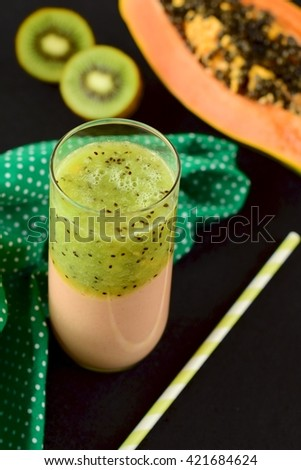 Papaya kiwi smoothie on black background