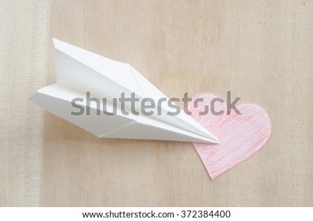 Paper airplane and paper heart on wooden table - stock photo