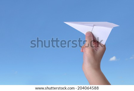 Paper airplane in children hand over sunny summer blue sky