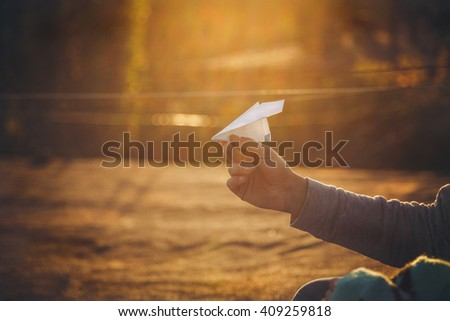 Paper airplane in man's hand at sunset - stock photo