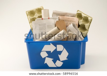 Paper and cardboard in a blue recycling bin. White background.