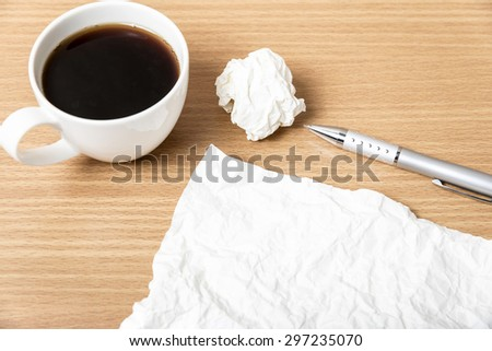 paper and crumpled with pen and coffee cup on wood background - stock photo