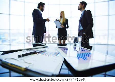 Paper and electronic financial documents at workplace on background of business partners interacting