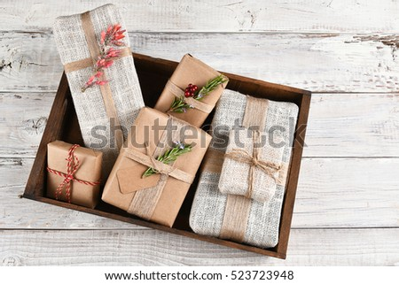 Paper and fabric wrapped Christmas presents in a wood box on a rustic whitewashed wood table.