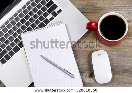 Paper and pen over laptop with coffee and mouse on side of rustic wooden desktop.  - stock photo
