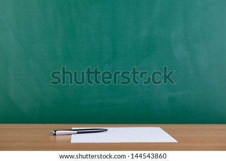 Paper and pen ready to be used on desk with blackboard in background