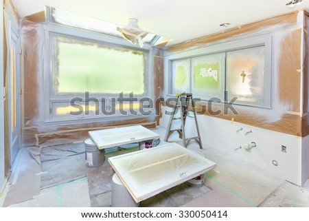 Paper and plastic masking for spray painting of kitchen during a remodel - stock photo