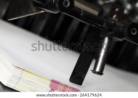 Paper and printing press after work - stock photo