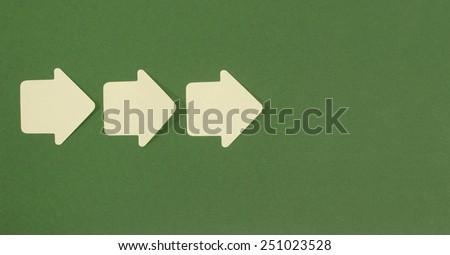 Paper arrows pointing forward. Yellow post it arrows on green background facing in front to the right. - stock photo