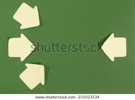 Paper arrows pointing inward. Yellow post it arrows on green background facing in. - stock photo