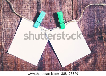 Paper attach to rope with clothes pins on wooden background - stock photo