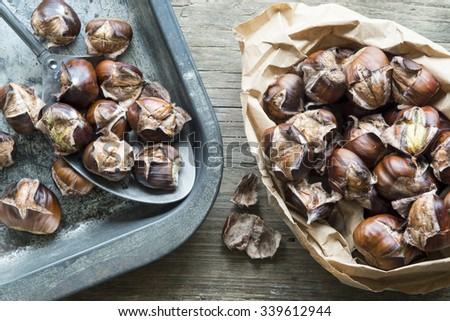 Paper bag and baking tray with freshly roasted chestnuts - stock photo