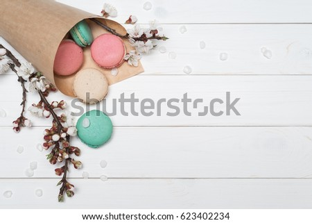 Paper bags with biscuits macaroon different colors. Delicious French dessert on a white wooden background. Branches with the flowers of apricot tree. Template for design. Flat layout, top view