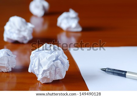 Paper balls and pen over blank white sheet - Creativity crisis concept  - stock photo