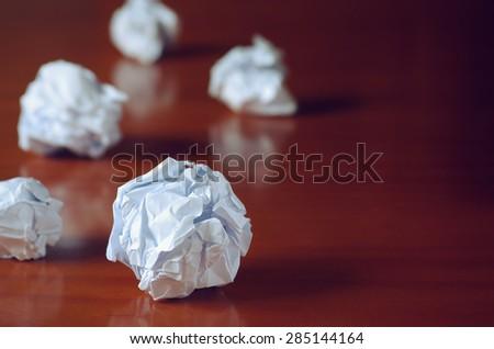 Paper balls over wooden table - Creativity crisis concept  - stock photo