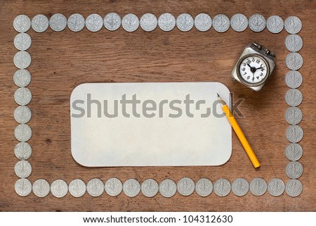 Paper blank and old clock on wood texture with antique silver coins frame - stock photo