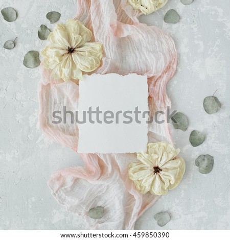 paper blank with dry white tulips, eucalyptus petals and pink textile on concrete background. Flat lay, top view