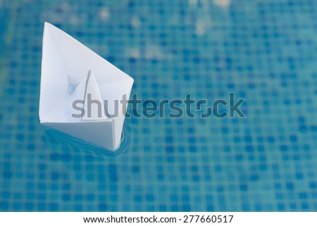 paper boat floating in blue water - concept of travel