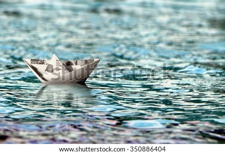 Paper boat floating on water - stock photo