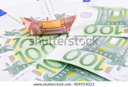 Paper boat floating over hundred euro bills