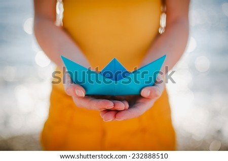 Paper Boat in female hands - stock photo