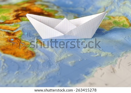 Paper boat on a background map of the world. Traveling concept - stock photo
