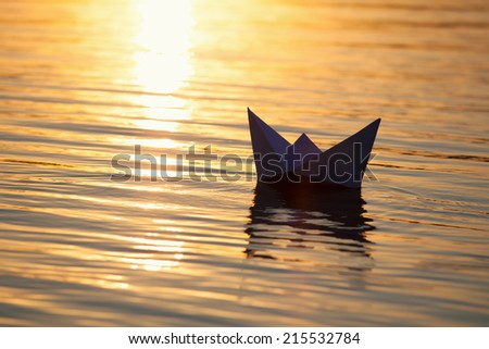 Paper boat sailing on water with waves  - stock photo