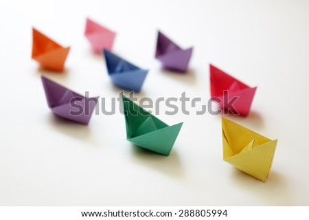 Paper boats of multi-colour following a leader boat concept for leadership, teamwork and winning success - stock photo