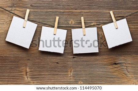 Paper card and clothes peg on a wooden background - stock photo