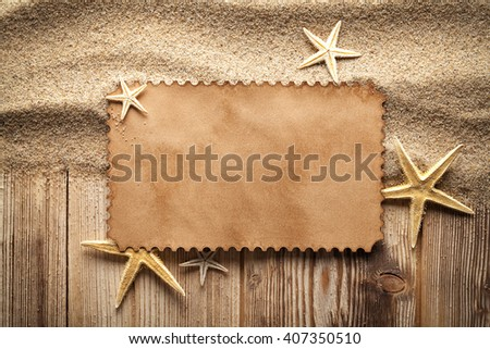 Paper card and starfishes on sand and wooden table