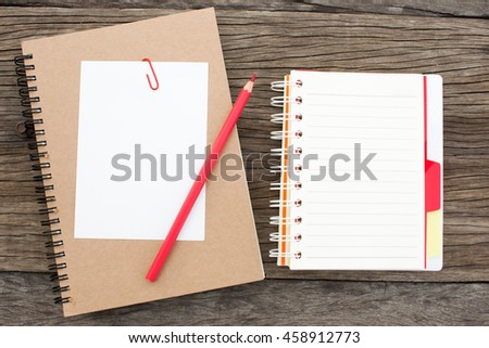 Paper card, pencil and notebook on wood table. top view for your text or artwork.