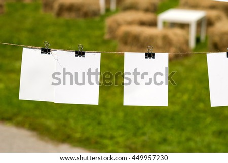 Paper cards hanging rope isolated on grass background