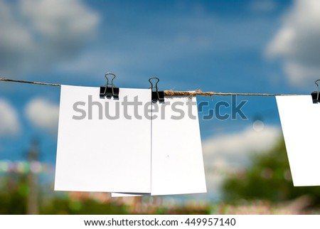 Paper cards hanging rope isolated on sky background