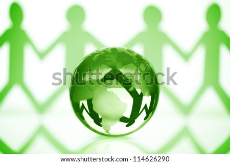 Paper chain men holding hands around a green globe concept for partnership, teamwork or global community - stock photo
