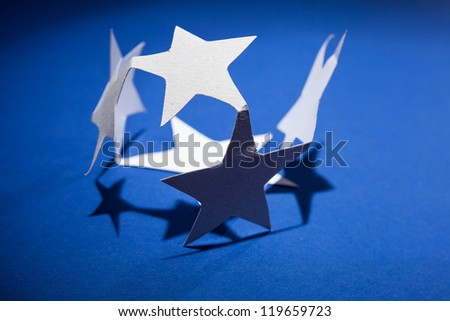 Paper christmas stars on the blue background .