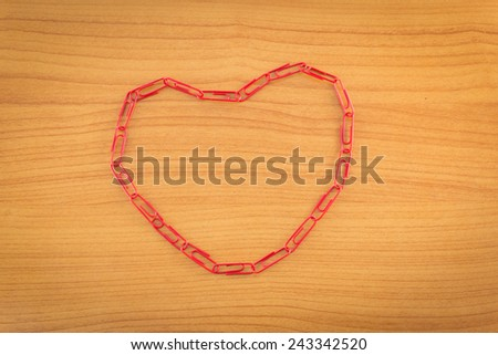 paper clips arranged in heart shape on wooden background. - stock photo