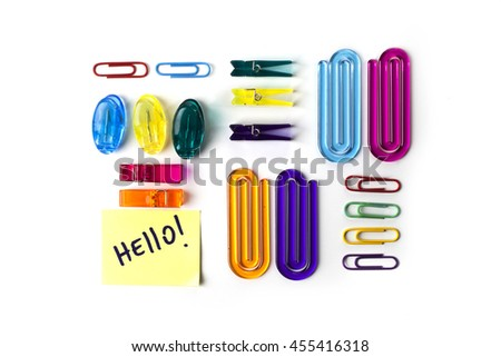 Paper clips set and yellow paper note with the words Hello isolated over a white background - stock photo