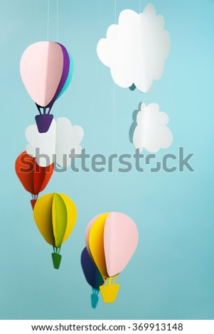 Paper clouds and airship on blue background - stock photo