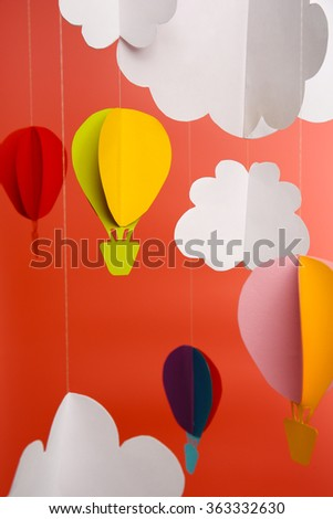 Paper clouds and airship on pink background - stock photo