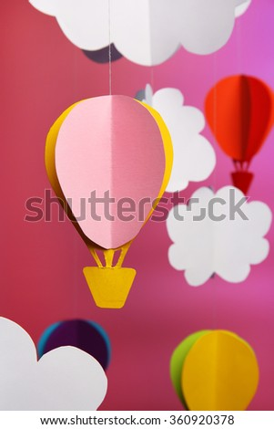 Paper clouds and airship on purple background - stock photo