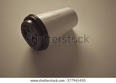Paper coffee cup  on white background, Shallow depth of field and Hipster color effect.