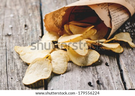 Paper cornet with potato chips with salt and pepper over old wooden table. See series - stock photo