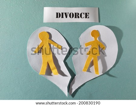Paper couple on ripped heart, with Divorce text                                - stock photo