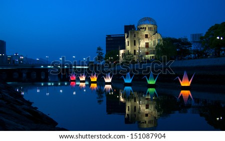Paper cranes floating in the water in front of Hiroshima nuclear bombing monument - stock photo