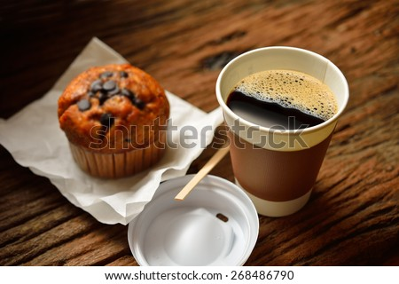 Paper cup of coffee and cake on wooden background - stock photo