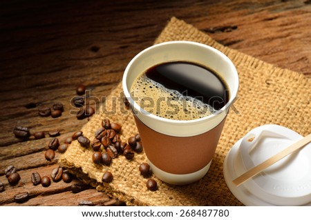 Paper cup of coffee and coffee beans on wooden table - stock photo