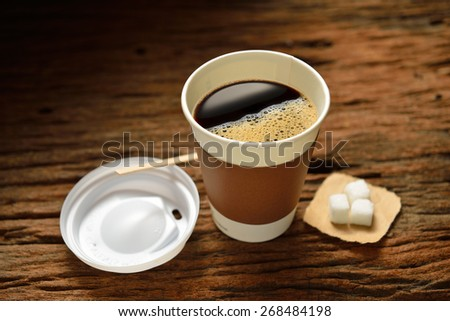 Paper cup of coffee and sugar cube on wooden background - stock photo