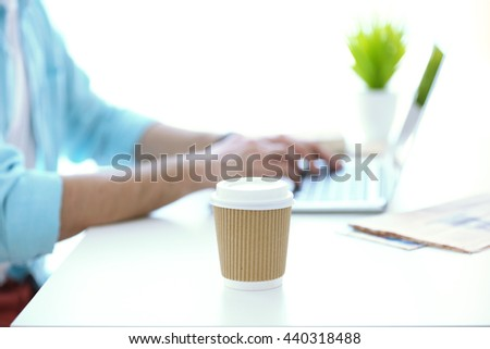 Paper cup of coffee and working man on background - stock photo