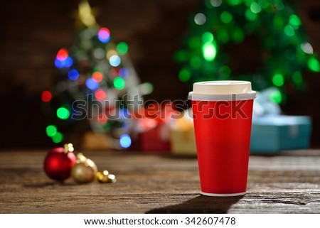 Paper cup of coffee surrounded by Christmas decorations on Christmas lights bokeh background  - stock photo