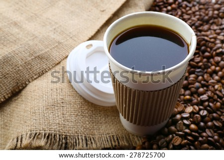 Paper cup of coffee with beans on sackcloth close up - stock photo